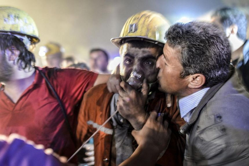 A miner is reunited with his father (right) after an explosion on May 13, 2014 in Manisa. -- PHOTO: AFP
