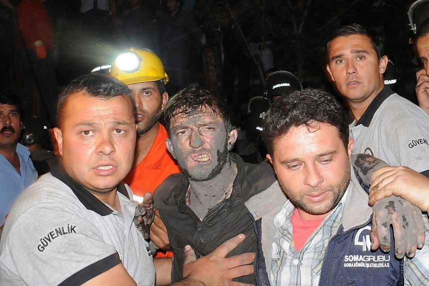 Miners assist an injured colleague after a mine explosion in Manisa, Turkey, on May 13, 2014. -- PHOTO: EPA