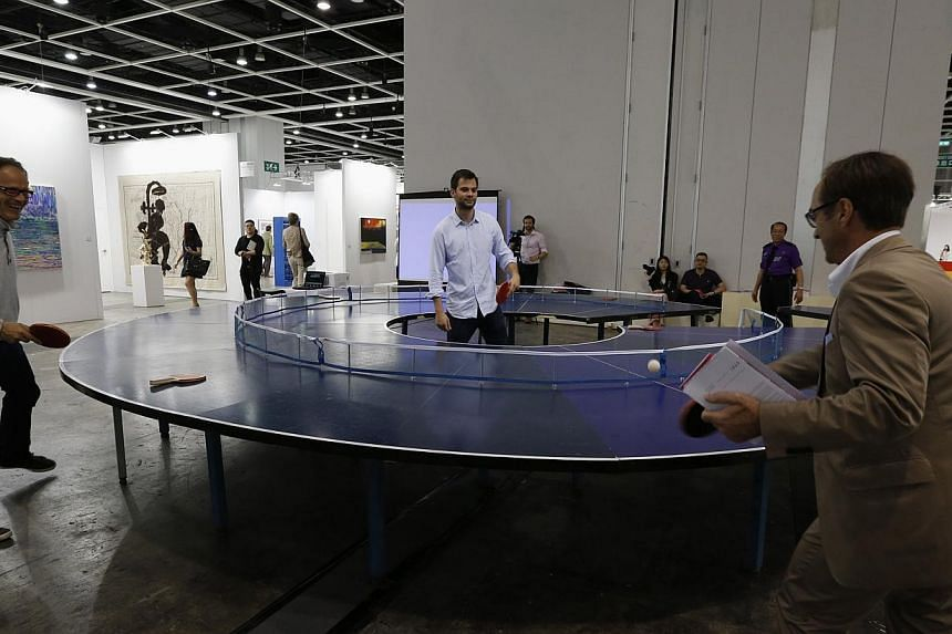"Visitors play table tennis on an artwork titled ""Ping Pong Go-Round"" by Singapore artist Lee Wen during the preview of Art Basel in Hong Kong on May 14, 2014. -- PHOTO: REUTERS"