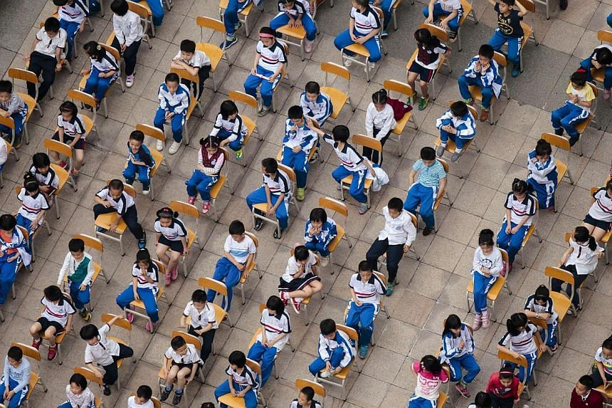 Students from different classes attend an outdoor joint lesson outside a school building in Guangzhou, Guangdong province on April 18, 2014.China's high-pressure, exam-driven education system is responsible for the vast majority of suicides by