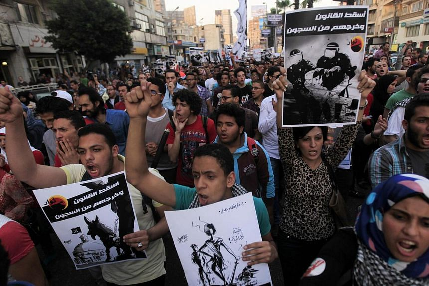 Members of the April 6 movement and liberal activists shout slogans against a law restricting demonstrations as well as the crackdown on activists, in front of El-Thadiya presidential palace in Cairo on April 26, 2014. A dissident movement which spea