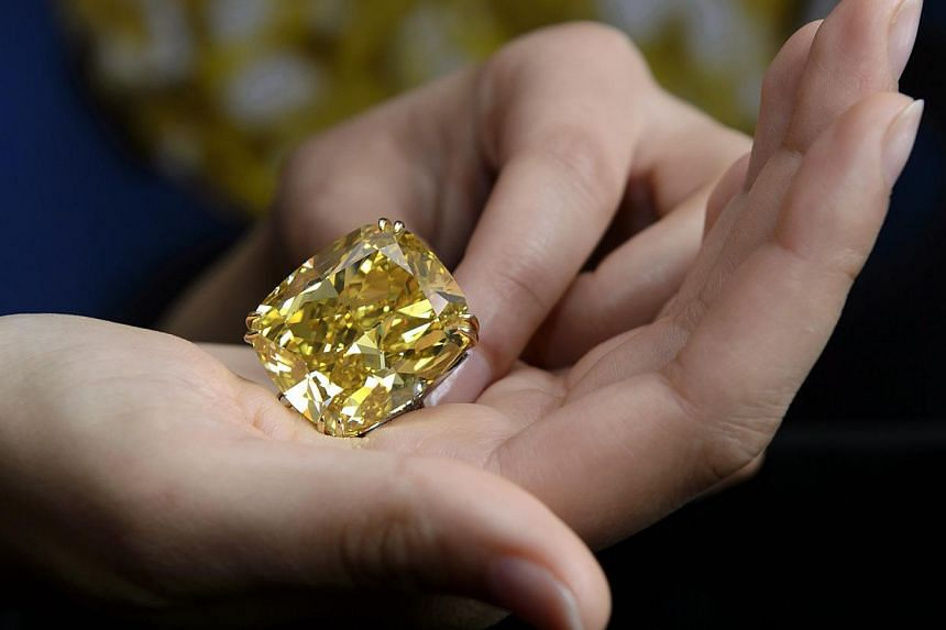 A Sotheby's employee shows The Graff Vivid Yellow at 100.09 carats, one of the rarest yellow diamonds of its size, during a press preview at the Sotheby's, in Geneva, Switzerland, on May 7, 2014. A 100-carat yellow diamond has sold for 14.5 million S