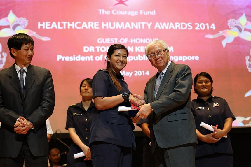 Ms Nurulelfyana Binte Badrulhisham, a paramedic, receives an Honourable Mention Award from President Tony Tan. A paramedic who conveyed the injured during the Little India riots, and a medical social worker who shielded his junior colleague and a pat