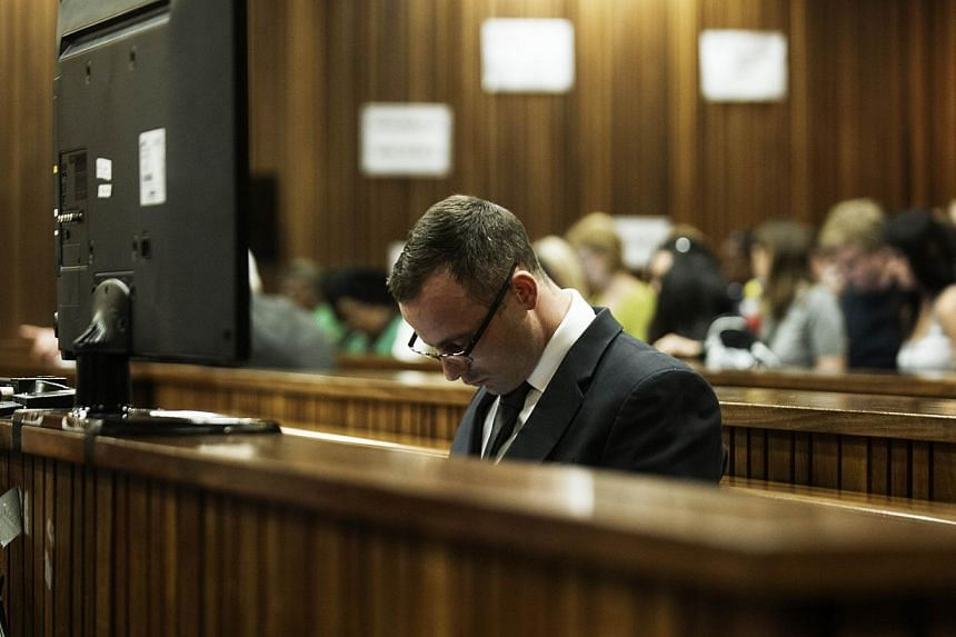 South African Paralympic sprinter Oscar Pistorius sits in the accused dock during his murder trial at North Gauteng High Court in Pretoria on May 14, 2014.  A South African judge on Wednesday ordered that Oscar Pistorius undergo psychiatric
