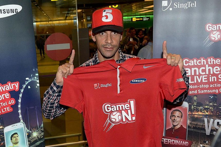 Manchester United's Rio Ferdinand poses with a shirt as he arrives at the Changi International Airport in Singapore on May 13, 2014 for the SG Game ON! Ultimate Selfie Challenge.-- PHOTO: AFP