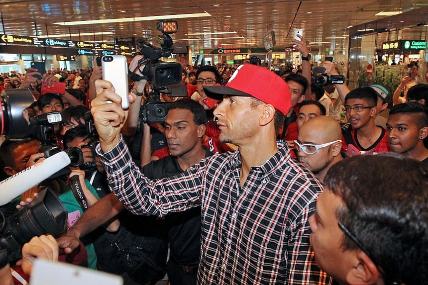 Former England captain Rio Ferdinand taking a selfie with fans during his arrival at Changi Airport on 13 May 2014. -- ST PHOTO:SEAH KWANG PENG