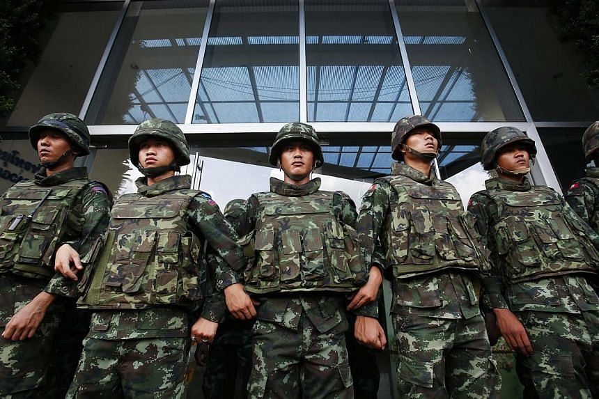 Soldiers stand guard against anti-government protesters outside the National Broadcast Services of Thailand (NBT) television station in Bangkok on May 9, 2014. The United States voiced confidence on Tuesday that Thailand's military will not stage a