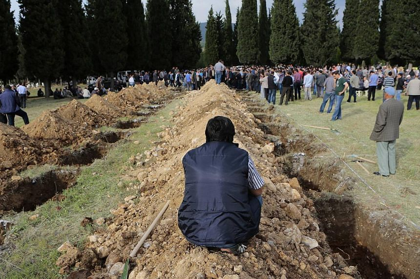 A man sits near graves during the funeral of a miner who died in a fire at a coal mine, at a cemetery in Soma, a district in Turkey's western province of Manisa on May 14, 2014. -- PHOTO: REUTERS