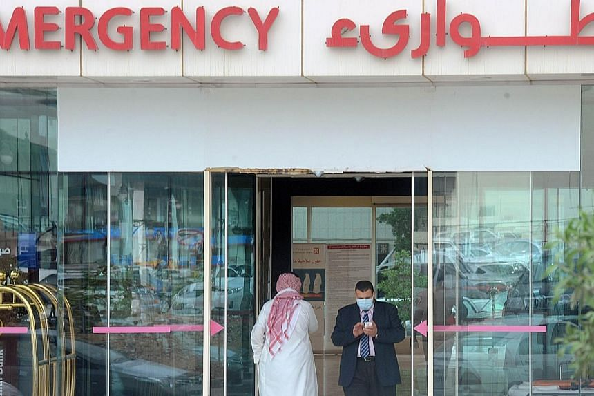 A man, wearing a mouth and nose mask, checks his phone as he leaves the hospital's emergency department on April 27, 2014 in the Saudi capital Riyadh. The Health Ministry will start temperature screening at air checkpoints for all passengers arr
