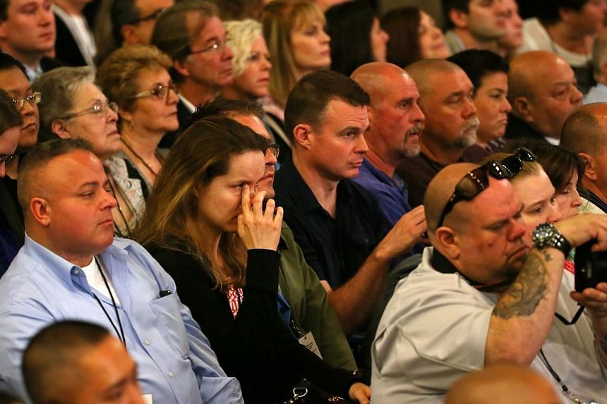 Invited family and friends of 9/11 victims react while United States President Barak Obama talks about Wells Crowther, who scarified himself to save others, during the dedication ceremony at the National September 11 Memorial & Museum in New York