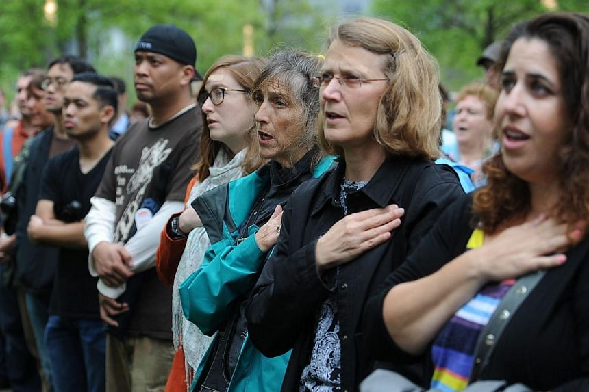 People react as they watch the screen projection of United States President Barack Obama giving a speech during the dedication ceremony at the National September 11 Memorial & Museum in New York on May 15, 2014. -- PHOTO: AFP