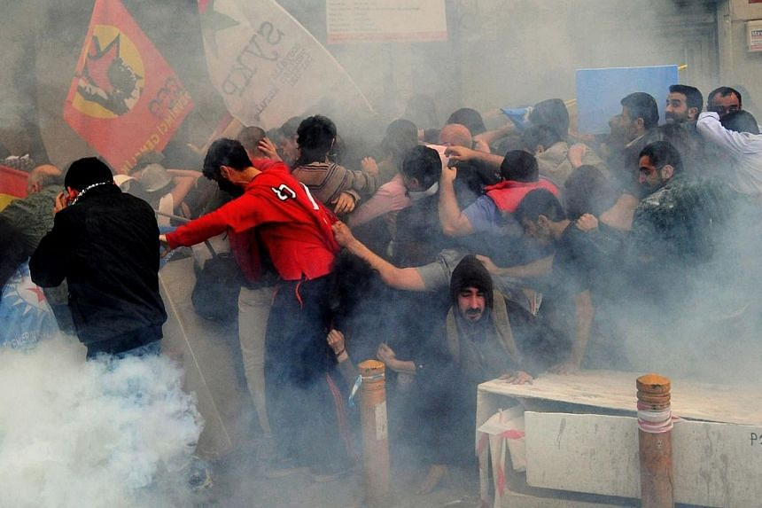 Protestors run away from tear gas during a protest on Istiklal avenue in Istanbul on May 14, 2014.Turkish police fired tear gas and water cannon at thousands of protesters on Thursday, as a 24-hour strike got underway over a deadly mine explosi