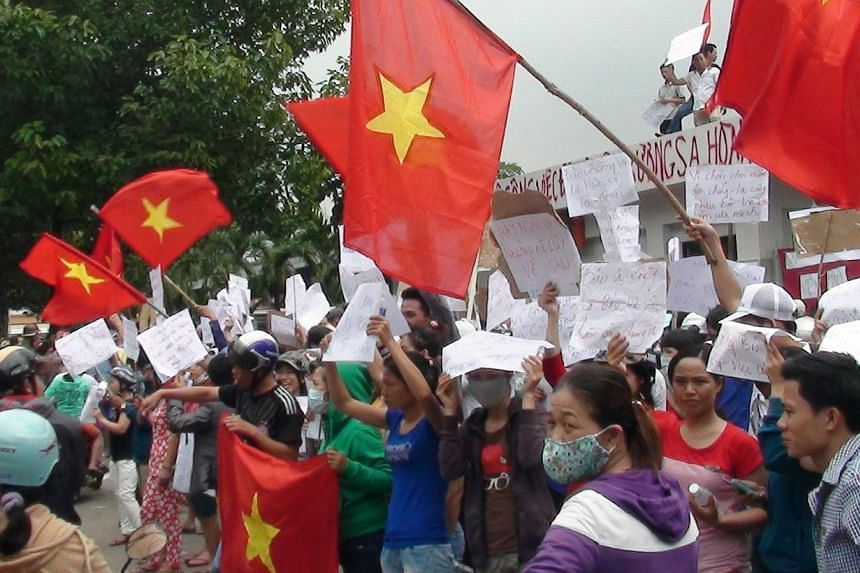 Protesters wave flags and hold placards on a street outside a factory building in Binh Duong on May 14, 2014, as anti-China protesters set more than a dozen factories on fire in Vietnam, according to state media, in an escalating backlash against Bei