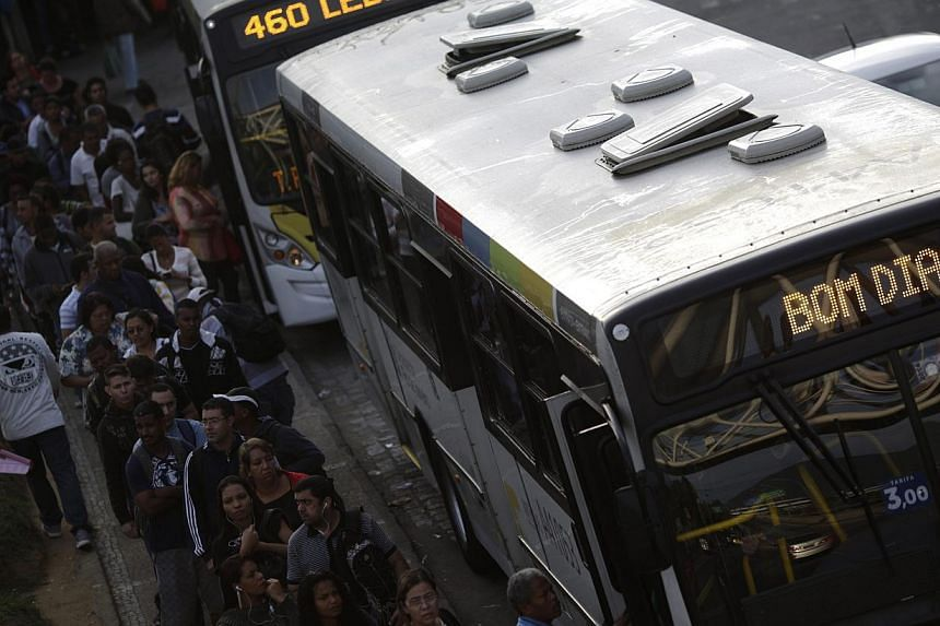 People wait in line to get into a bus during a 48-hour bus strike in Rio de Janeiro on May 14, 2014. The strike renewed concerns about services and public order one month before Rio and 11 other Brazilian cities play host to the upcoming World Cup so