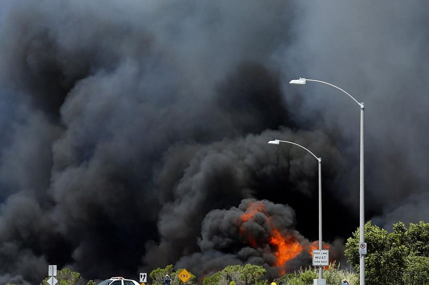 A wildfire burns through a canyon in Carlsbad, California on May 14, 2014. -- PHOTO: REUTERS