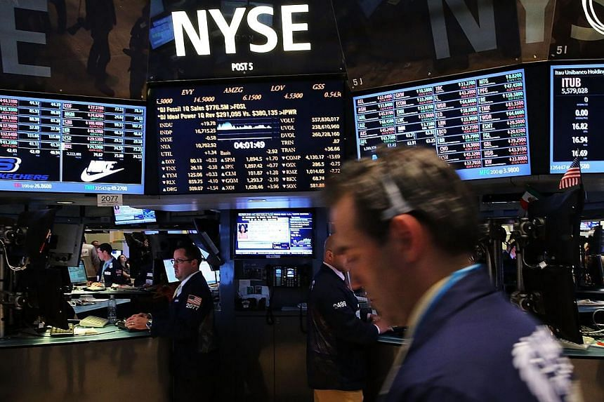US stocks finished lower following mixed earnings and a surprising rise in producer prices, snapping a five-day winning streak for the Dow that included three straight record closings. -- PHOTO: AFP