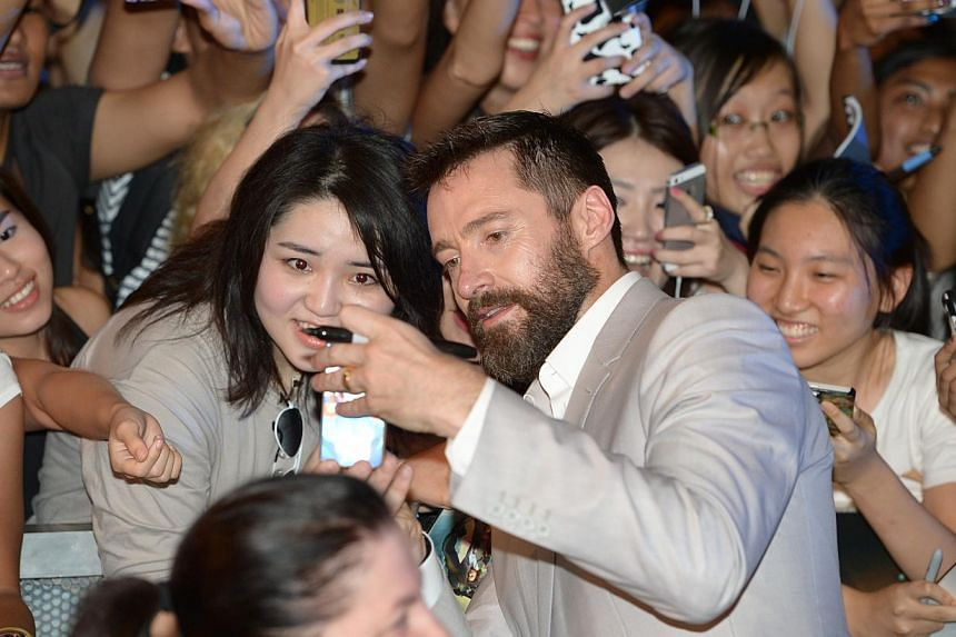 Actor Hugh Jackman snapping a selfie with a fan at the South-east Asian premiere of X-Men: Days Of Future Past, at Shaw House in Orchard Road yesterday. -- ST PHOTO: DESMOND WEE