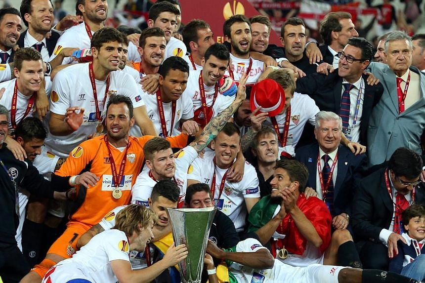 Sevilla's captain Ivan Rakitic (left) and his teammates celebrate with the trophy after the UEFA Europa League 2014 final between Sevilla FC and Benfica Lisbon in Turin, Italy, on 14 May 2014. Sevilla won 4-2 on penalties. -- PHOTO: EPA