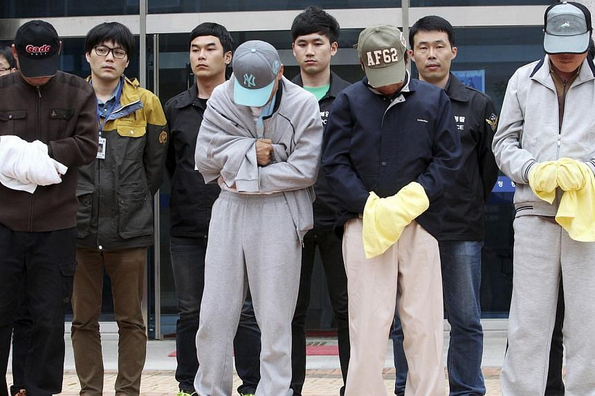 Crew members (front row) of the sunken Sewol ferry stand outside a court in Mokpo, after investigators sought for warrants of their arrest at the court on April 26, 2014. -- FILE PHOTO: REUTERS