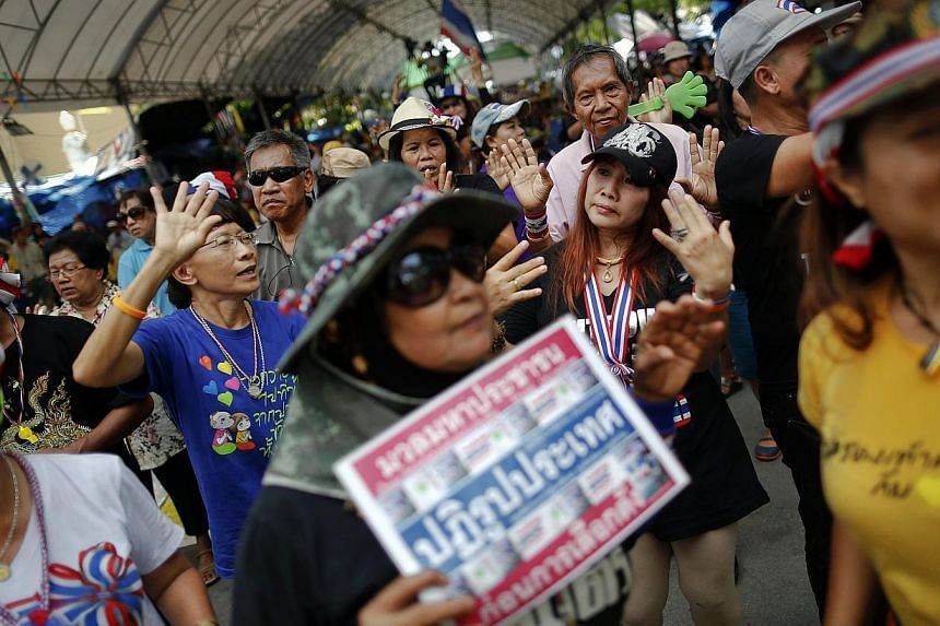 Anti-government protesters dance during a rally in an area protesters are occupying around the Government House in Bangkok on May 14, 2014. Two anti-government protesters were killed and 21 were wounded in a gun and grenade attack early Thursday