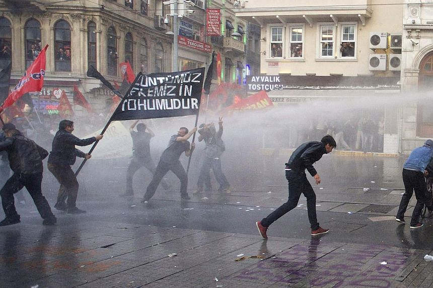 Protesters run away from water canon fired by the riot police during a demonstration blaming the ruling AK Party (AKP) government for the mining disaster in western Turkey, in central Istanbul on May 14, 2014. Turkish police fired tear gas and water
