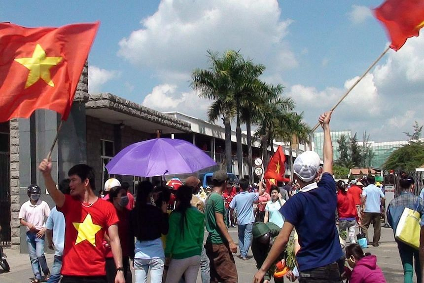 A photo made available May 14, 2014 shows workers waving Vietnamese flags outside a factory in the Binh Duong province, Vietnam, on May 13, 2014. -- FILE PHOTO: EPA