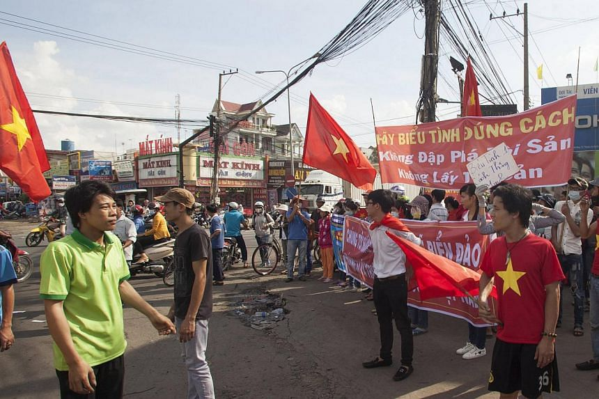 Workers wave Vietnamese national flags during a protest at the industrial zone in Binh Duong province on May 14. -- PHOTO: REUTERS