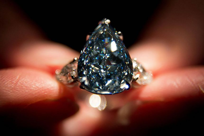 "This photo taken on April 29, 2014, shows a Christie's auction house employee holding ""The Blue"", the largest flawless vivid blue diamond in the world, during a photocall at the auction house in London. The world's largest blue diamond known as ""The"