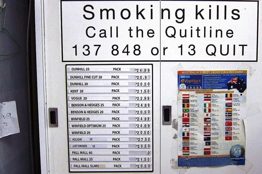 A sign to discouraging smoking is seen on a cabinet above a list displaying prices for the cigarettes inside it at a small shop in central Sydney on April 4, 2014. Australia has some of the toughest tobacco laws in the world, with firms forced t