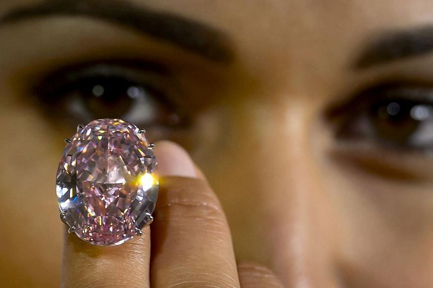 A model shows during a press preview on September 25, 2013 a 59.6-carat pink diamond that was auctioned by Sotheby's in Geneva in November, 2013 -- FILE PIX: AFP