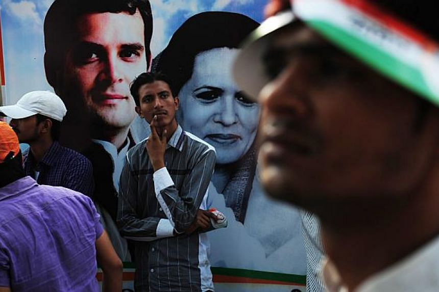 An Indian man stands in front of a poster affixed to a truck showing portraits of Congress Party Vice President Rahul Gandhi (Top L) and Rahul's mother and Congress President Sonia Gandhi (C) during the final day of campaigning in the Indian election