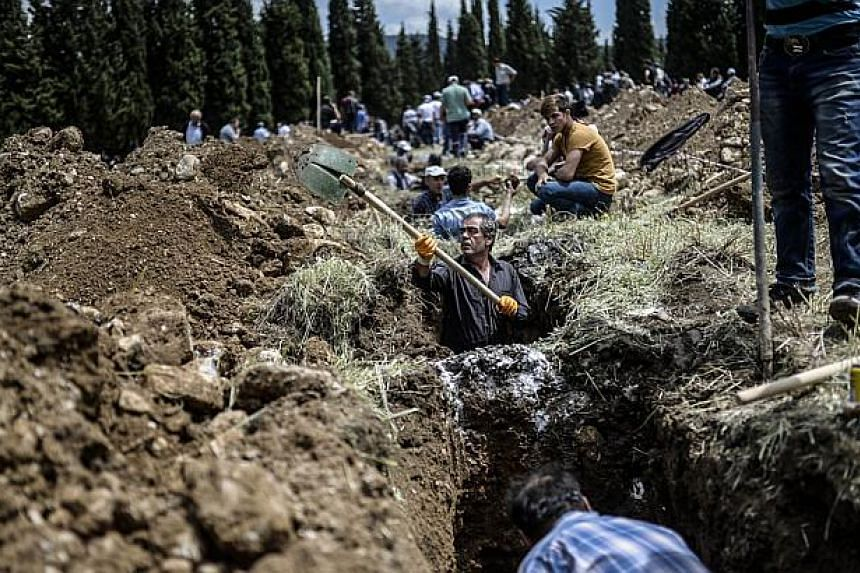 People dig graves for miners in a cemetery during the funeral ceremony of miners who died in an explosion on May 15, 2014, in the western town of Soma in the Manisa province. -- PHOTO : AFP
