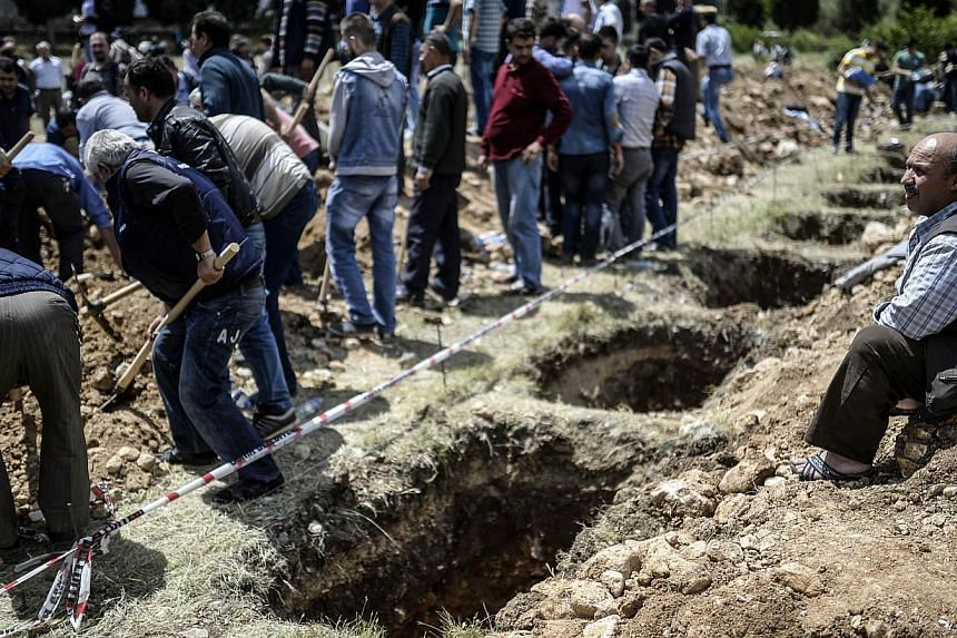 People gather around empty graves during a funeral ceremony of miners who died in an explosion on May 15, 2014, in the western town of Soma in the Manisa province. -- PHOTO : AFP