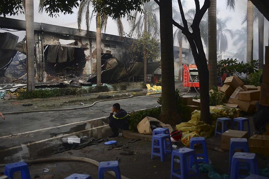 Firefighters rest near a damaged Chinese owned shoe factory in Vietnam's southern Binh Duong province on May 14, 2014.Beijing on Thursday, May 15, 2014, accused Hanoi of acting in concert with anti-China protestors who have killed at least one Chines