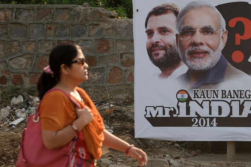An Indian pedestrian walks past a hoarding featuring images of Bharatiya Janata Party (BJP) prime-ministerial election candidate Narendra Modi and Congress Party prime-ministerial candidate Rahul Gandhi on a roadside in New Delhi on May 16, 2014. --
