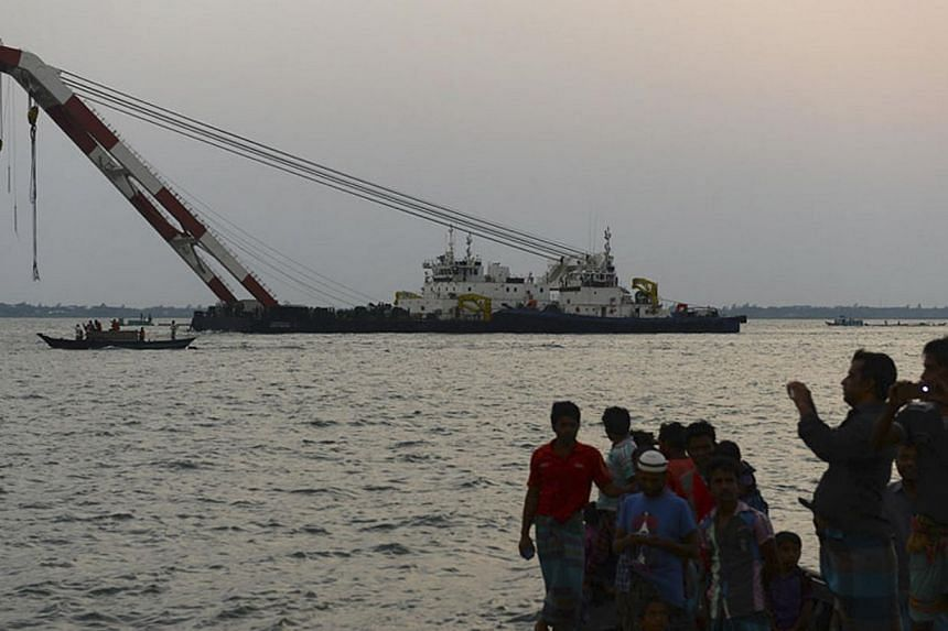 People watch and take pictures as a rescue vessel tries to provide help to the M.V. Miraj-4 ferry that capsized in high winds and rain in the Meghna river at Rasulpur in Munshiganj district on May 15, 2014. The Bangladeshi river ferry with around 200