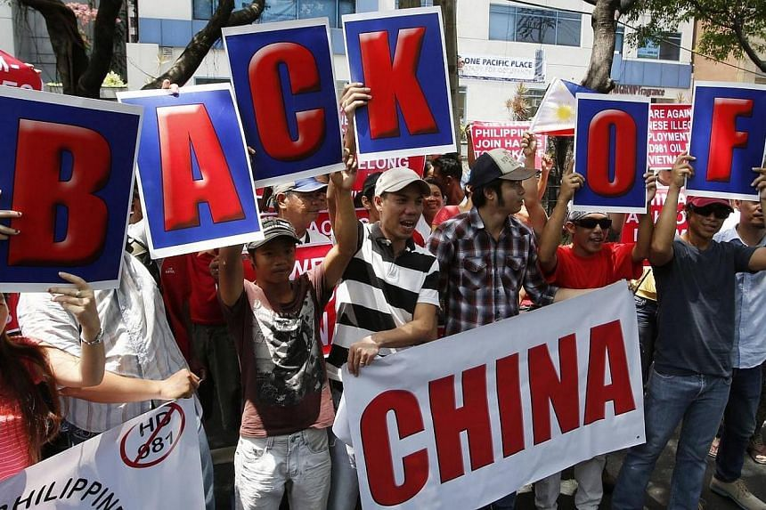 Filipino activists and Vietnamese nationals display placards and chant anti-China slogans as they march outside the Chinese Consulate in Manila's Makati financial district on May 16, 2014.Several hundred Filipino and Vietnamese protesters unite
