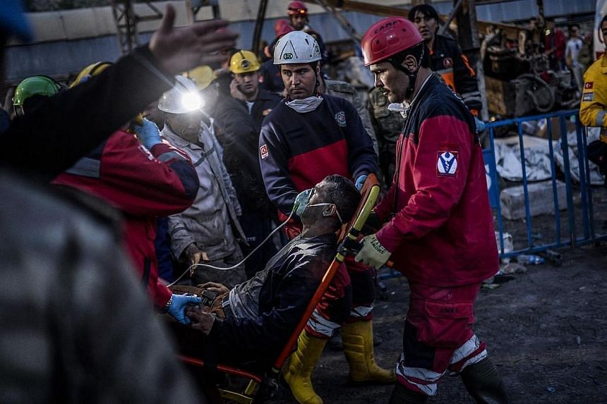 Rescuers evacuate a colleague after inhaling smoke on May 15, 2014, two days after an explosion in a coal mine at Soma in Manisa. A maximum of 18 people are still believed to be trapped in a Turkish coal mine following a blast which killed more than