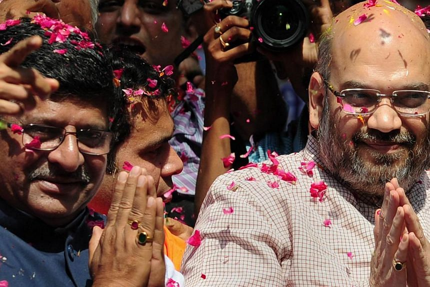 Senior Bharatiya Janata Party (BJP) leaders Amit Shah (R) and Ravi Shankar Prasad (L) greet supporters as they celebrate victory at their party's headquarters in New Delhi on May 16, 2014. -- PHOTO: AFP