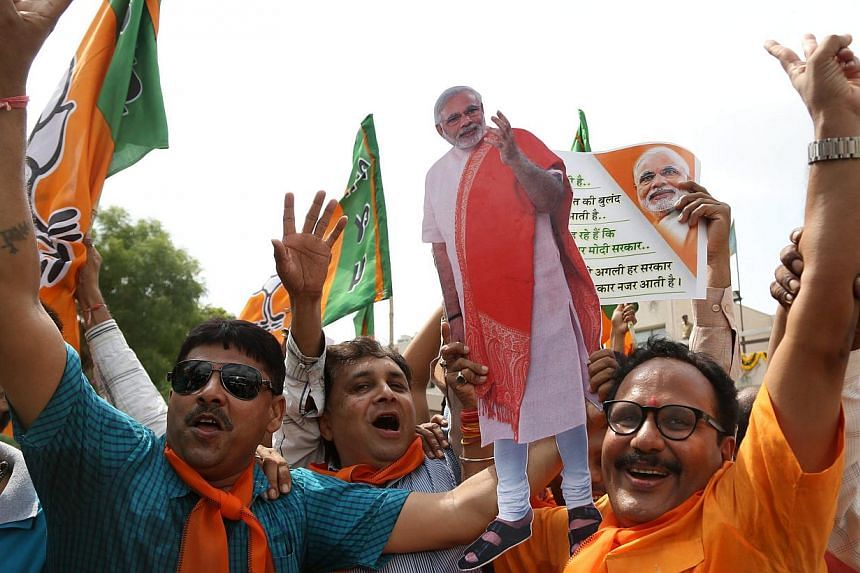 Supporters celebrate the Bharatiya Janata Party's performance in India's general election, at the party's state headquarters in Gandhinagar, the capital of Gujarat. -- PHOTO: EPA