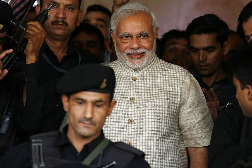 Bharatiya Janata Party's prime ministerial candidate and Gujarat Chief Minister Narendra Modi is escorted by security personnel at the party's state headquarters in Gandhinagar, Gujarat, on May 16, 2014. Election results, still being coun