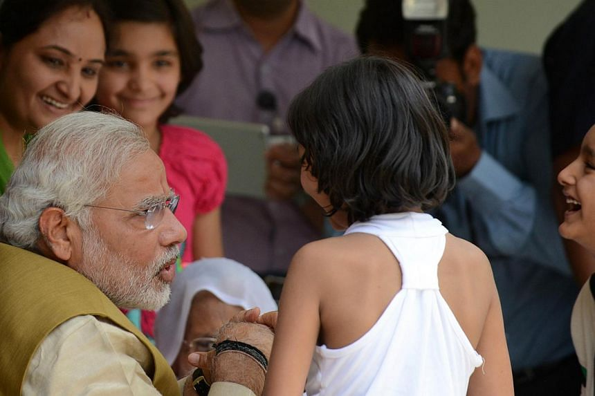 The Chief Minister of India's western Gujarat state and main opposition Bharatiya Janata Party (BJP) prime ministerial candidate, Mr Narendra Modi, interacts with his brother's children at the home of his mother Hira Ba in Gandhinagar, about 23 kms f