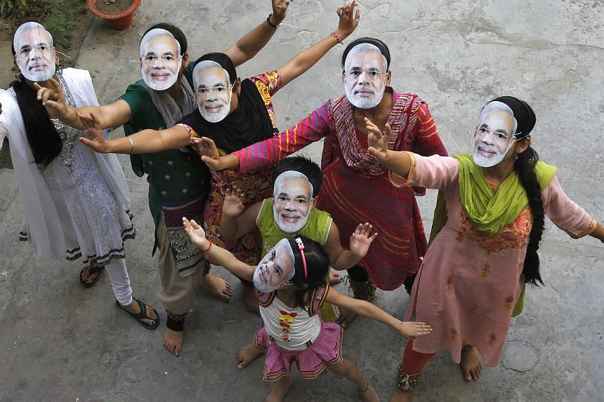 Supporters wearing masks of Hindu nationalist politician Narendra Modi, the prime ministerial candidate for India's main opposition Bharatiya Janata Party (BJP), celebrate after learning of initial poll results in the northern Indian city of Allahaba