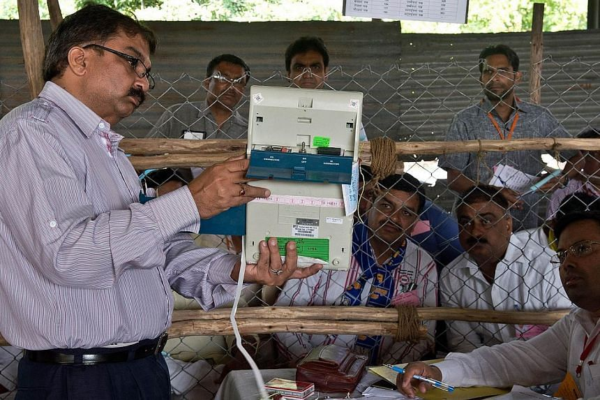 An Indian election official shows the results on an Electronic Voting Machine (EVM) to polling agents at a counting centre in Ghaziabad on May 16, 2014. Early counting trends show a big mandate for the opposition Bharatiya Janata Party (BJP) and Hind