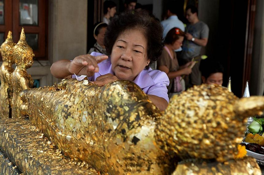 A Thai devotee anoints gold leaves onto a Buddha statue as an offering at Wat Pho, one of the largest and oldest in Bangkok, on February 22, 2014. Residents ofKhao Luang district of Loei province, near the northern border with Laos,have f