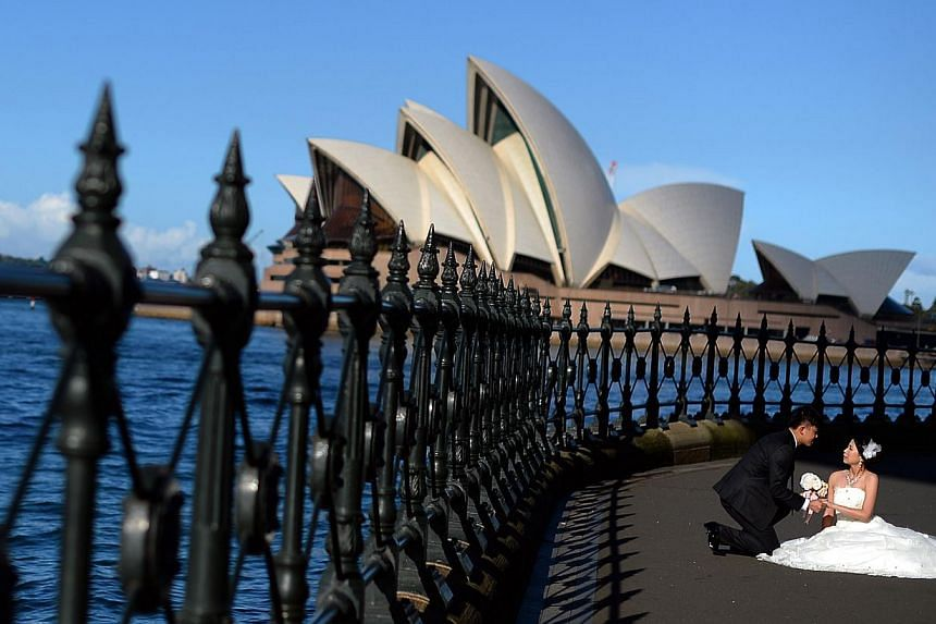 This picture taken on May 13, 2014 shows a bride and groom posing in front of Sydney's iconic land mark Opera House during their photo shoot. -- PHOTO: AFP