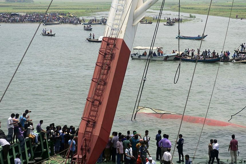 Bangladeshi rescuers work to raise a capsized ferry which sank during bad weather on the Meghna river in Munshiganj district, some 50 kilometres south of Dhaka on May 16, 2014. Divers battled on Friday to recover bodies trapped in the wreckage of a B