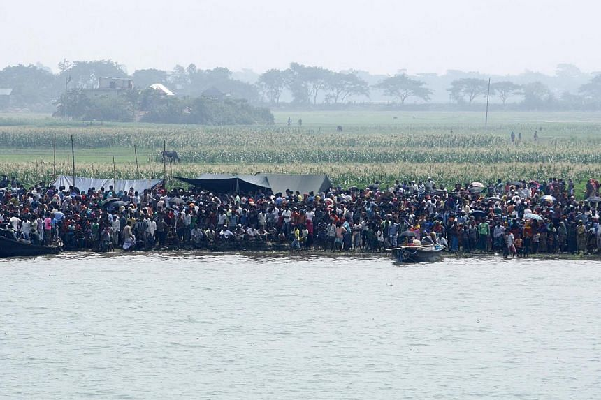Relatives and locals stand on the shore as they watch the rescue work of the sunken ferry MV Miraj 4 at the Megna River near Munshiganj, Bangladesh, on May 16, 2014. -- PHOTO: EPA