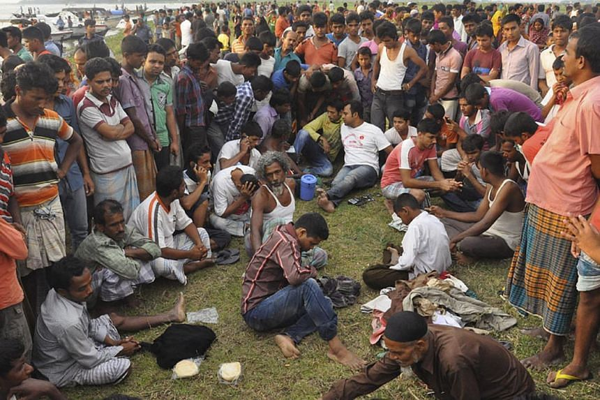 Relatives wait for news of the passengers after the M.V. Miraj-4 ferry capsized, by the Meghna river at Rasulpur in Munshiganj district on May 15, 2014. -- PHOTO: REUTERS