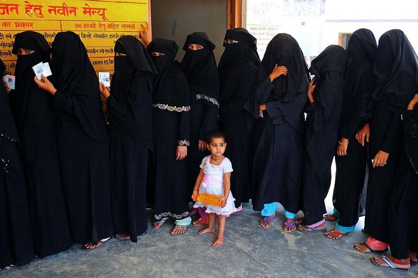 A child looks on as Indian Muslim voters wait in line to cast their ballots at a polling station in Azamgarh, about 275 kms from Lucknow in northern Uttar Pradesh state, on May 12, 2014. He has been pilloried for horrific riots in which hundred